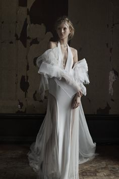 Light ivory halter neck silk georgette gown with sheer French tulle inserts at the skirt. Styled with silk organza floral sleeve.