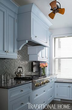 New blue-painted cabinets and glimmering glass tiles update this kitchen with a…