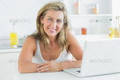 Smiling woman sitting in the kitchen and using laptop ...  30s, Looking At Camera, Mid Adult, background, blonde, blue eyes, caucasian, computer, content, fair hair, female, happy, indoors, kitchen, laptop, light eyes, light hair, long hair, notebook, shelves, sink, smiling, straight hair, table, technology, typing, using, wireless, woman