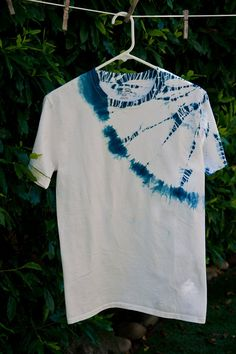 Boys Shibori designed dyed T-shirt  This is a BOYS shirt, sized S/P by Champion  This shirt is a 100% Cotton, hand dyed Indigo. The last 2 images are of the back of the shirt. :)  It is soft and super easy summer wearing. Easy care, no ironing required. This is a hand dyed product. The dye is not perfect, has imperfections, and no two shirts will ever be the same even if they are they same general design. I think this makes them special. All shirts are pre-washed, machine wash and dry, no…