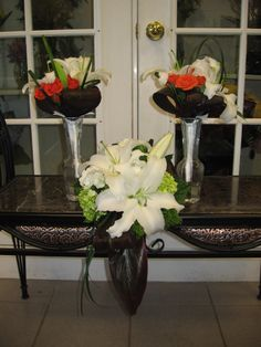 Oriental lilies, orange ranunculus, green hydrangea, ti leaves