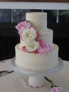 Three tier round buttercream wedding cake with textured grooves and live flowers