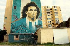 Martin Ron in front of 'El Apache' that he painted with Lean Frizzera and Emy Mariani