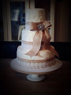 Rustic vintage themed wedding cake. Three tiers covered in vanilla buttercream. Decorated with hessian/burlap ribbon and bow, finished with antique lace and a crystal brooch.
