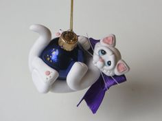 This white cat is hugging a hot pink Christmas ball. If desired, I can add a name to the Christmas ball.  Measuring 2 1/4 inches wide and 2 inches tall, this cutie comes with a gold cord for hanging on the Christmas tree.  Each of my creations are made from a mixture of polymer clay and are hand sculpted without the use of molds. Also, all of my ornaments and figurines come with a gift box so all you have to do is wrap some ribbon around the box and you are ready to give a special keepsake…