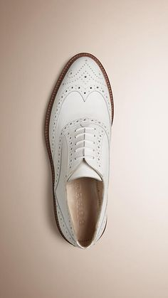 Italian-made Burberry white leather brogues with traditional perforated wingtip detail.