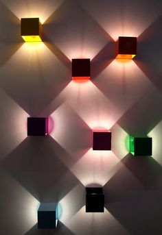 'lux W1' wall-mounted lighting system. the modular design is made up of colored aluminium cubes (100x100x100mm), which when lit, project an outward triangular light. the units can each make full 360 degree rotations, and in combination with one another, create multi-colored geometric patterns on the wall.