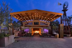The+wood+pergola+with+string+lights+adds+dimension+and+definition+to+a+dining+area+with+two+picnic-style+tables+and+a+massive+fireplace.+Other+elements+that+fit+into+the+modern+design+are+the+pergola,+use+of+steel+and+concrete,+and+decorative+elements+such+as+barrels.