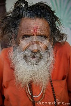 Portrait of an old man with beard, Indian sadhu in orange robes
