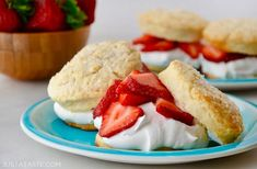 Easy Strawberry Shortcakes with homemade whipped cream on blue plate with small wooden bowl filled with fresh strawberries in background.