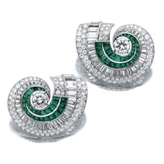 PAIR OF EMERALD AND DIAMOND CLIPS, 1950S. Each of scroll design, set with baguette, circular-, single- and brilliant-cut diamonds and calibré-cut emerlads, mounted in platinum, signed Gompers, French assay and maker's marks.