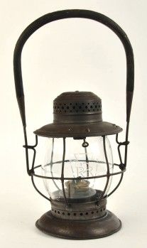 """Unmarked bellbottom lantern marked """"SOLD ONLY BY T.L. MOORE SAN ANTONIO TEX."""" with patent date of 1906. Lantern is the unusual switchman's design with relatively low profile and rigid wooden handle that does not collapse down as well as drop-out fount. Globe is a Macbeth Pearl Glass 223 Barrel Globe with PRR Keystone etched logo, and large piece cracked out of bottom. Height to top of handle approx. 14"""", to top of dome 8.5"""". size: 14"""" t."""
