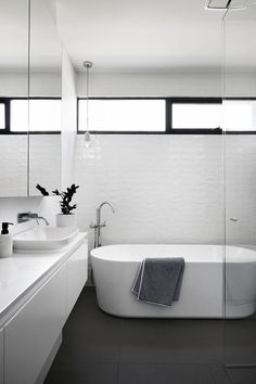 This modern and simple black and white bathroom has slightly textured white tiles, a standalone bathtub and a walk-in glass shower. window Sisalla Interior Design Complete A New Home In Melbourne Ensuite Bathrooms, Laundry In Bathroom, Bathroom Renos, Budget Bathroom, Bathroom Renovations, White Bathrooms, Bathroom Windows, Shower Bathroom, Mirror Bathroom