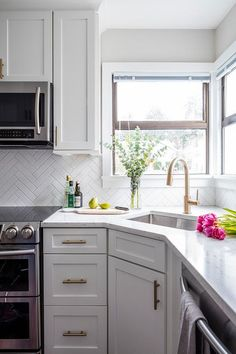 Lovely little corner kitchen sink with a brass gooseneck faucet under two windows surrounding white shaker cabinets and brass pulls.