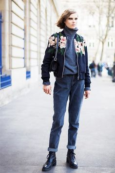 Caroline Brasch Nielson wears a casual outfit with a grey turtleneck, cuffed jeans, and tops it off with a floral bomber jacket.