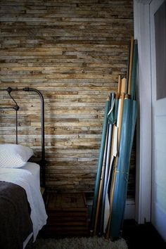 Dig this reclaimed wood wall, especially with a simple iron bed.