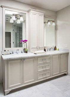 Gorgeous master bathroom features a light grey double vanity adorned with polished nickel knobs ...
