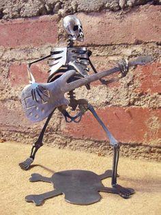 Zombie Skeleton Playing Electric Bass Guitar Metal Sculpture.