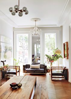 In the living room of the brownstone shared by menswear designer Robert Geller and his wife, Ana, the minimalist chairs by Phase Design in the living don't compete with the almost-ceiling-height windows that look out onto their tree-lined Fort Greene, Brooklyn, street, which help to bring the outside in.