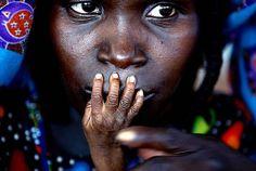 1 de agosto de 2005 – Tahoua, Níger. La imagen muestra los ojos perdidos de una mujer refugiada en un centro de alimentación en Níger y la pequeña mano de su bebé que le cubre la boca. Su autor manifestó que simboliza el silencio al que están sometidas las personas más desamparadas en ese país.