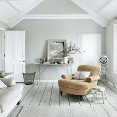 Cool and relaxing living room    As a place to chill out, this room is hard to beat. The understated coastal atmosphere - created by the grey and white-painted flooring, open beams and deep linen-covered armchair - makes it ideal for quiet contemplation.    Armchair - Sofa.com  Light - Alexander & Pearl  Console table - Andy Thornton  Paint - Farrow & Ball