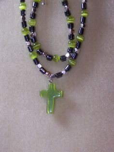 Magnetic hematite with cross necklace and bracelet set. Accented in lime green tigers eye beads and silver spacers. Button clasps.