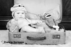 5 month old baby boy sitting in a suitcase with a monkey hat on.