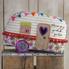 Camper Boho Mattress Ticking Pillow - Camper-shaped mattress ticking pillow with burlap door and window, felt flag banner and tomato red pompoms. Super-soft dusty purple corduroy fabric on the back makes this fun room accessory perfect for an afternoon nap.