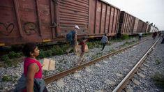 Migrants walk along railroad tracks after getting off