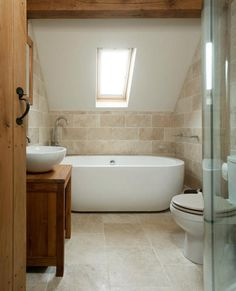The  rustic stone and simple, modern tub and sink surprisingly complement each other gorgeously!