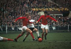 England captain Bobby Moore combines with Martin Peters to clear the ball in front of West German striker Uwe Seeler during the FIFA World Cup Final...