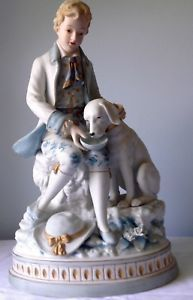 Pair of large porcelain bisque figurines of a boy and girl and their dogs