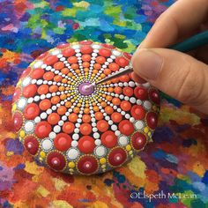 Elspeth McLean putting the finishing dot on a mandala stone #mandalastone #elspethmclean #dotillism