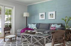Aqua blue and charcoal gray living room features an accent wall clad in aqua grasscloth lined with a charcoal sofa with chaise lounge accented with aqua trellis pillows, purple ikat pillow and a purple throw blanket placed next to a driftwood end table with glass top.