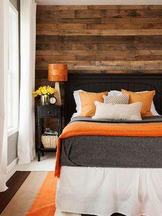 hölzerne wand und orange dekokissen auf einem bett