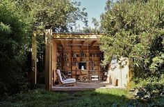 Backyard shed that functions as both a work space and a library, with retractable doors and view of the garden.  Gardenista.com