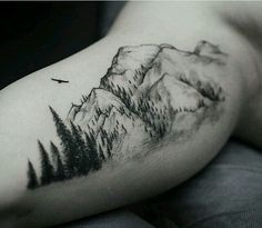 Mountains & forest tattoo with the words adventure awaits underneath it