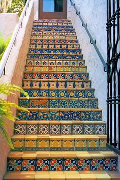 Cheerfully tiled risers on staircases make them less of a chore to climb. Love the colors!