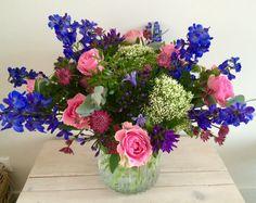 Boeket met roze rozen, blauwe delphinium, witte trachelium, paarse campanula