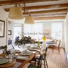 At one end of the dining room is a breakfast table with a linen-covered Empire sofa and a pair of antique chairs