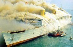 Hong Kong Harbor, January 9, 1972. Seawise University, the former RMS Queen Elizabeth, burns, with the Alexander Grantham fighting the fire.