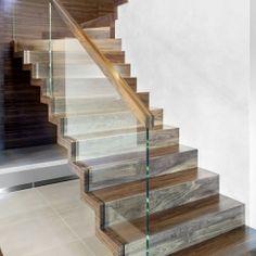 www.trabczynski.com  ST872 Schody dywanowe wykonane z orzecha amerykańskiego, częściowo osadzana na wylewce betonowej. Balustrada ze szkła z drewnianym pochwytem. Realizacja wykonana w domu prywatnym , projekt – TRĄBCZYŃSKI