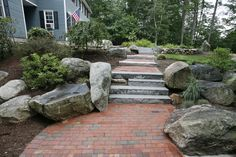 A brick walkway boasting granite steppers surrounded by gorgeous landscaping with boulders accents.