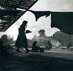 Ernst Haas. AUSTRIA 1947. Silhouetted women in headscarves prepare food in a makeshift home on the streets of Vienna after the end of WW II.
