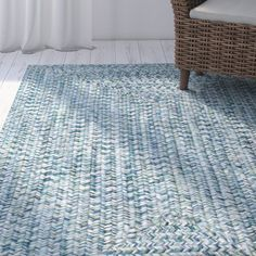 Lend a breezy touch to your mudroom or patio with this lovely rug, featuring a braided design in cool blue tones.