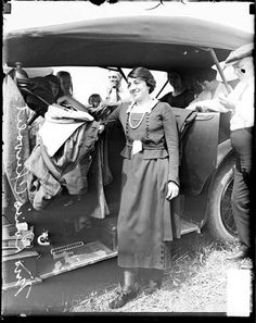 Mrs. Louise Chevrolet standing outdoors next to an automobile in Elgin, Illinois, during the 1920 Elgin automobile race.