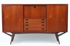 """Elegant Danish Sideboard  Danish sideboard/ hutch circa early 1960′s. This elegant example has a drop down door with a glass backed interior. There are four drawers beneath the drop down door with inset solid teak handles and two large sliding doors with adjustable interior shelves. The legs of this chest are truly striking as well.    Measurements  Height: 50"""" x Width: 78.75"""" x Depth: 17.25""""  Price  $4800  View more items in categories:  Bookcases, Buffet, Cabinets, Chest, Furniture…"""