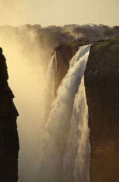 "Victoria Falls (""the Smoke that Thunders"") is a waterfall in southern Africa on the Zambezi River at the border of Zambia and Zimbabwe."