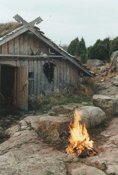 the patina of the wood of this aged shed is lovely.. shown of by the vibrant color of the fire