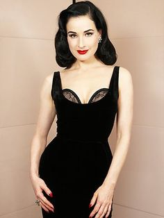 Dita Von Teese, in the 'Showcase' dress from the Muse collection. A black velvet, sleeveless sheath dress, very fitted.